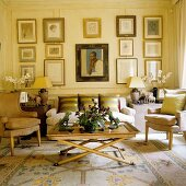 A living room in a period building with a coffee table, a sofa and an armchair in front of a collection of pictures