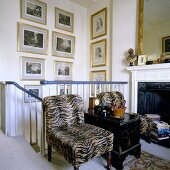Armchairs with fur covers against a banister rail in front of a fireplace and pictures in gold frames hanging on the wall of the stairwell