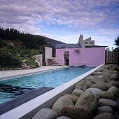 A long pool in front of a house with boulders at the poolside and a pink-painted wall