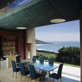 Dining area in front of a wall of window with a fantastic view of the ocean