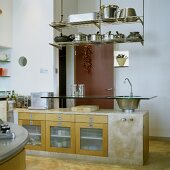 A concrete kitchen counter with a built-on glass bar with an integrated sink and a suspended shelf