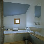 An attic bathroom with a blue ceiling - a wash basin and a built-in bathroom with circumferential metal cladding