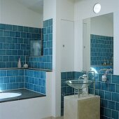 Blue wall tiles in a niche with a built-in bathtub and a glass sink on a concrete pedestal with a mirror above