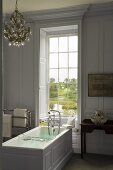 An elegant bathroom in a country house with a free-standing bathtub in front of a window with a view