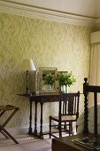 A bedroom with a table lamp on an antique wall table standing against a wall hung with floral wallpaper