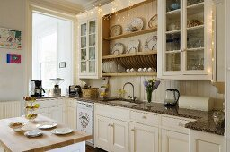A white country house kitchen with cabinets, a plate rack and an island counter