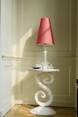 A table lamp with a red shade on a white occasional table with curved base standing against a wood panelled wall