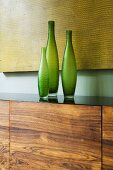 Green vases on a wooden side board in front of a yellow picture