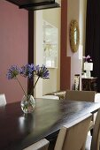 Flowers in a glass vase on a wooden dining table and a dark red wall