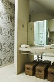An open wash area - baskets under a wash basin in front of a mirror and a partition wall to the side