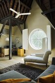 A white chaise longue in front of a round window with shutters in a converted attic with a dark wooden ceiling