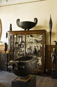 A metal container on a pedestal and a cabinet containing a collection of African handicrafts