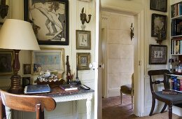 A table lamp with a white shade on an antique desk standing against a wall next to an open door providing a view into a hallway