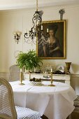 Brass candle sticks on a dining table laid with a white cloth and a chandelier with glass bead decoration