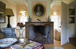 An open-plan, country house-style living-cum-dining room with a sooty fireplace and view of transom windows