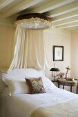 A bed room in a country house with a white wood beams and a canopy over the bed