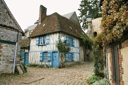 An old half-timbered house with blue window shutters on the corner of a street