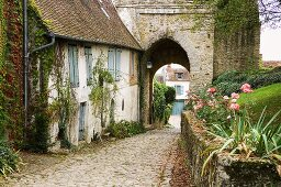 An old house with closed shutters and a cobbled road leading through a medieval gate