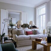 A coffee table and a light upholstered sofa in a living room with a view through open swing doors