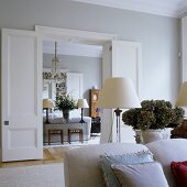 An elegant living room and dining room with light grey walls