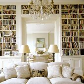 A light upholstered sofa in front of a built-in bookshelf with a view into a living room