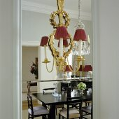 A brass chandelier with red shades mounted on a mirror in which a black dining and chairs are reflected
