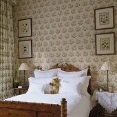 An antique wooden bed in a traditional English bedroom with wallpaper and matching curtains
