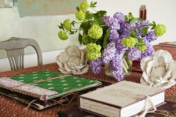 A bunch of lilac and colourful folders on a table with a patterned tablecloth