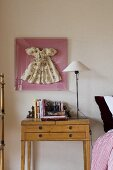 A table lamp with a white shade on a light wood bedside table with a framed doll's dress hanging on the wall