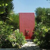 A dark red wall with a water spout in a Mediterranean garden