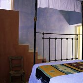 A Mediterranean bedroom with a blue wall and flight of steps
