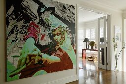 A contemporary picture on a wall and a view through to an open door of a living room with a continuous parquet floor