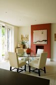 An elegant living with white upholstered chairs and a round glass table in front of a fireplace in a red wall