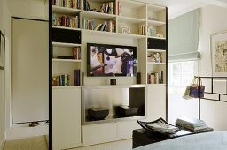 A floor-to-ceiling shelf-cupboard as a room partition in an open-plan bedroom