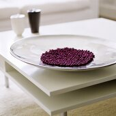 Violet beads in a shiny dish on a white coffee table