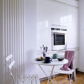 Breakfast in front of a white built-in cupboard with a built-in oven