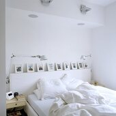 A bed with white bedclothes and a picture gallery in a wall niche and pivotable table lamps