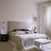 A white bedroom with a Bauhaus-style double bed with a padded leather headrest and a stool at the end of it