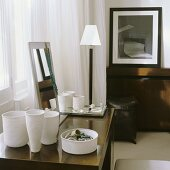 White handmade pots and a jewellery dish on a wooden table next to an elegant floor lamp with a white shade