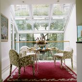 Patterned, upholstered armchairs in front of a designer table in a conservatory with a view