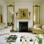 A living room with a fireplace and a comfortable upholstered armchair in front of a floor-to-ceiling mirror with a gold frame