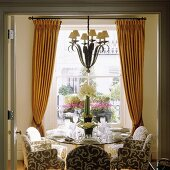 A set table in front of a window with pleated, yellow curtains with a chandelier hanging in the middle