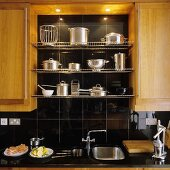 Kitchen cupboards with wooden doors with stainless steel pans on a wire shelf in a black-tiled niche