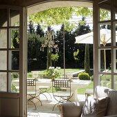 A view through an open terrace door onto elegant outdoor furniture and a Mediterranean garden