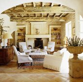 A view through a rounded archway in a Mediterranean living room with a rustic wood beam ceiling and white armchairs in front of a natural stone fireplace