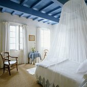 A white canopy above a queen-sized bed in a bedroom in a country house with a blue ceiling
