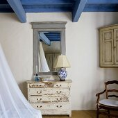 An old fashioned chest of drawers in front of a framed mirror in a room with a blue wooden ceiling