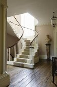 Curved staircase with carpet runner and busts on a pedestal in a stairway