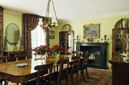 An elegant dining room with green wall and a long wooden table in front of a fireplace