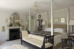 Antique sofa bed in front of a four poster bed in an elegant bedroom